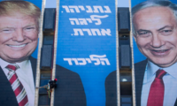 An Israeli worker hangs a campaign billboard of President Donald Trump shaking hands with Prime Minister Benjamin Netanyahu on a Jerusalem building