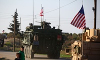 U.S. military vehicles on a road in Syria, showing the American flag.