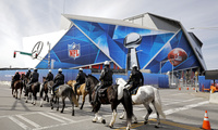 Police on horseback patrol past Mercedes-Benz Stadium