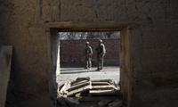 Security personnel are framed in a damaged door