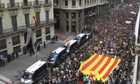 Protesters hold a Catalan flag as they gather outside National Police Headquarters in Barcelona