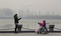 Visitors in a park gesture at each other near chimneys spewing smoke in Beijing, China