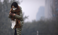 A woman wears a face mask as she looks at her smartphone while walking along a street in Beijing
