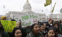 Students yell and hold up signs at a rally for clean energy in San Francisco