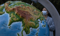 woman wearing a mask looks at a globe showing China