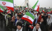Children wave Iranian flags during a ceremony celebrating the 40th anniversary of the Islamic Revolution in Azadi Square