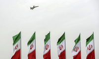 A fighter jet flies over Iranian flags