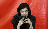 A woman uses her cell phone at Tehran's International Book Fair