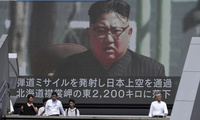 a public TV screen showing a file footage of Kim Jong Un