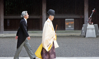 Japanese Prime Minister Junichiro Koizumi follows a Shinto priest toward the sanctuary of the Yasukuni war shrine