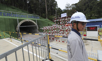A worker stands near a tunnel