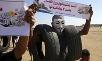 A protester wears a mask while carrying tires to burn near the fence of the Gaza Strip border
