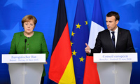 French President Emmanuel Macron, right, and German Chancellor Angela Merkel speak at a news conference in Brussels