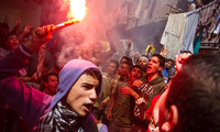 An Egyptian youth carries a lit flare