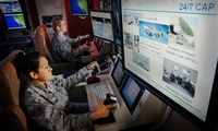 U.S. Air Force Master Sgt. Jennifer Oberg, background, a communications maintenance instructor, and Senior Airman Raquel Martinez, foreground, check a ground control station during training