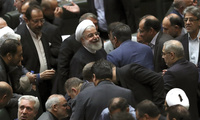 Iranian President Hassan Rouhani listens to a lawmaker