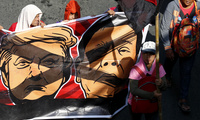 Protesters march with crossed out caricature of U.S. President Donald Trump and Philippine President Rodrigo Duterte