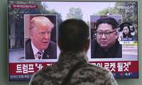 a TV screen showing images of U.S. President Donald Trump, left, and North Korean leader Kim Jong Un