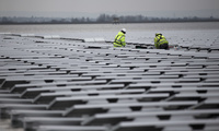contractors continue work on floating solar panel array