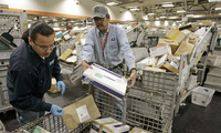 U.S. Postal Service mail handlers Alan Flores, left, and Romeo Gumpal sort packages.