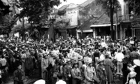 Viet Minh troops are surrounded by civilians as they enter Hanoi