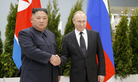 Russian President Vladimir Putin, right, and North Korea's leader Kim Jong Un shake hands