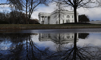 The White House is reflected in a puddle,